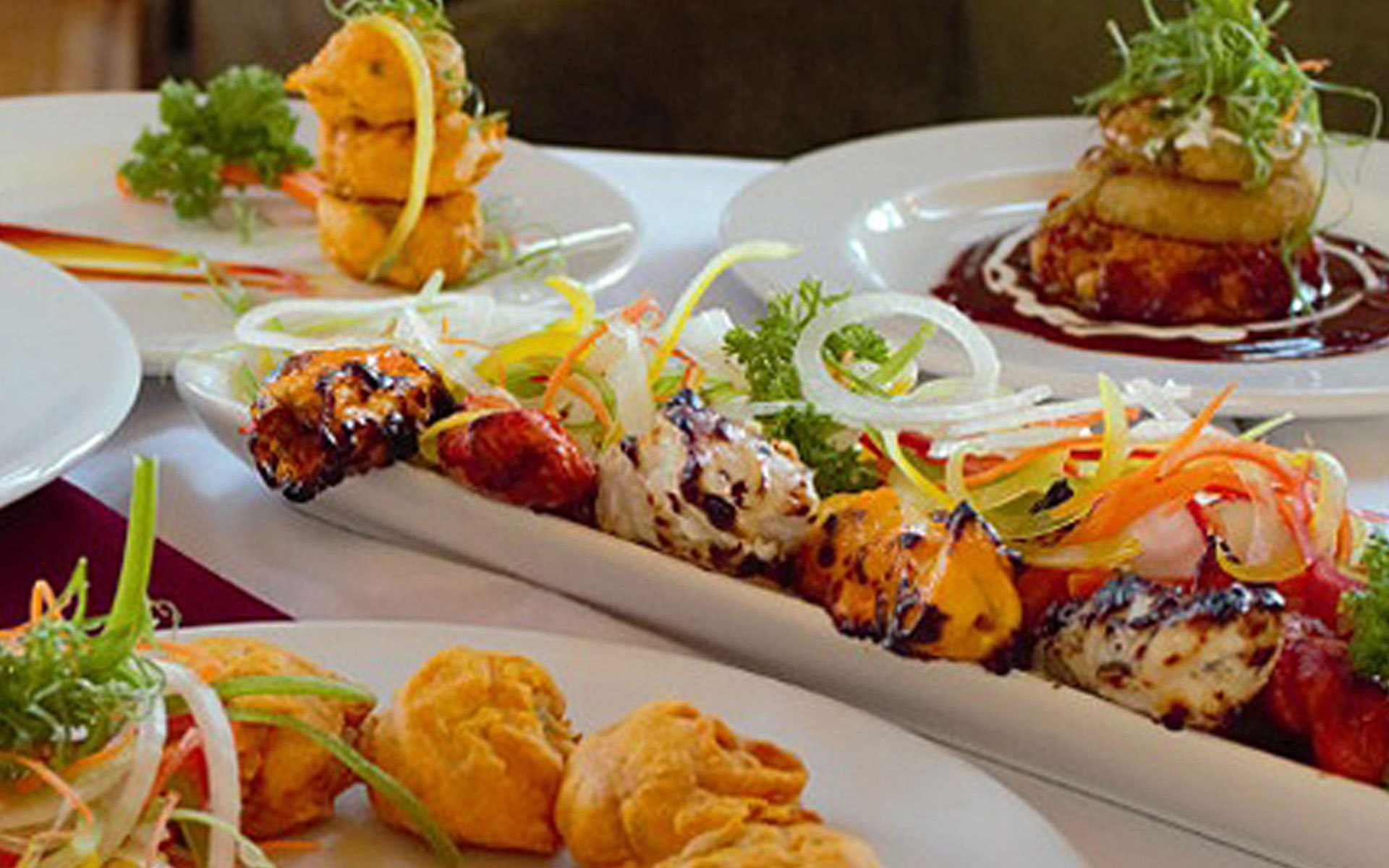 Plates of tikkas and samosas garnished with onion rings, curly green onion strings and parsley are served alongside bhuna, a dish of chicken, onions, tomatoes and bell peppers at Tandoor & Grill at the Stanford Fernie Resort.