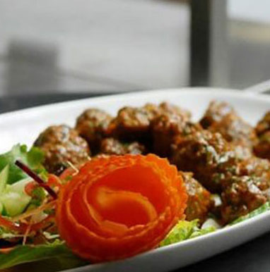 The Tandoor & Grill Restaurant located onsite at the Stanford Fernie Resort serves classic dishes such as lamb rogan josh with greens and tomato garnish.