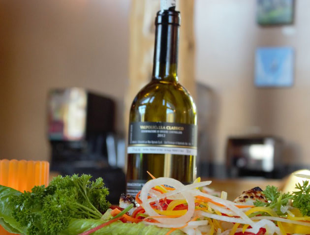 A bottle of wine is placed behind a dish garnished with parsley, onion rings, red and yellow bell pepper slices at the Tandoor & Grill Restaurant located at the Stanford Fernie Resort in British Columbia.