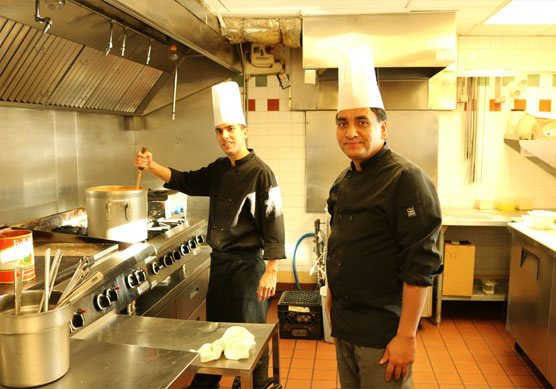 Two male chefs wearing tall white chef's hats stand alongside multiple cooking ranges in the kitchen of the Tandoor & Grill Restaurant located onsite at the Stanford Fernie Resort.