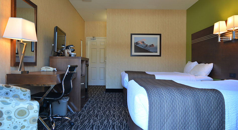 The Economy Room at the Stanford Fernie Resort features two queen sized beds with a flower print white cover opposite a honey colored wood writing desk and a flatscreen TV placed on top.