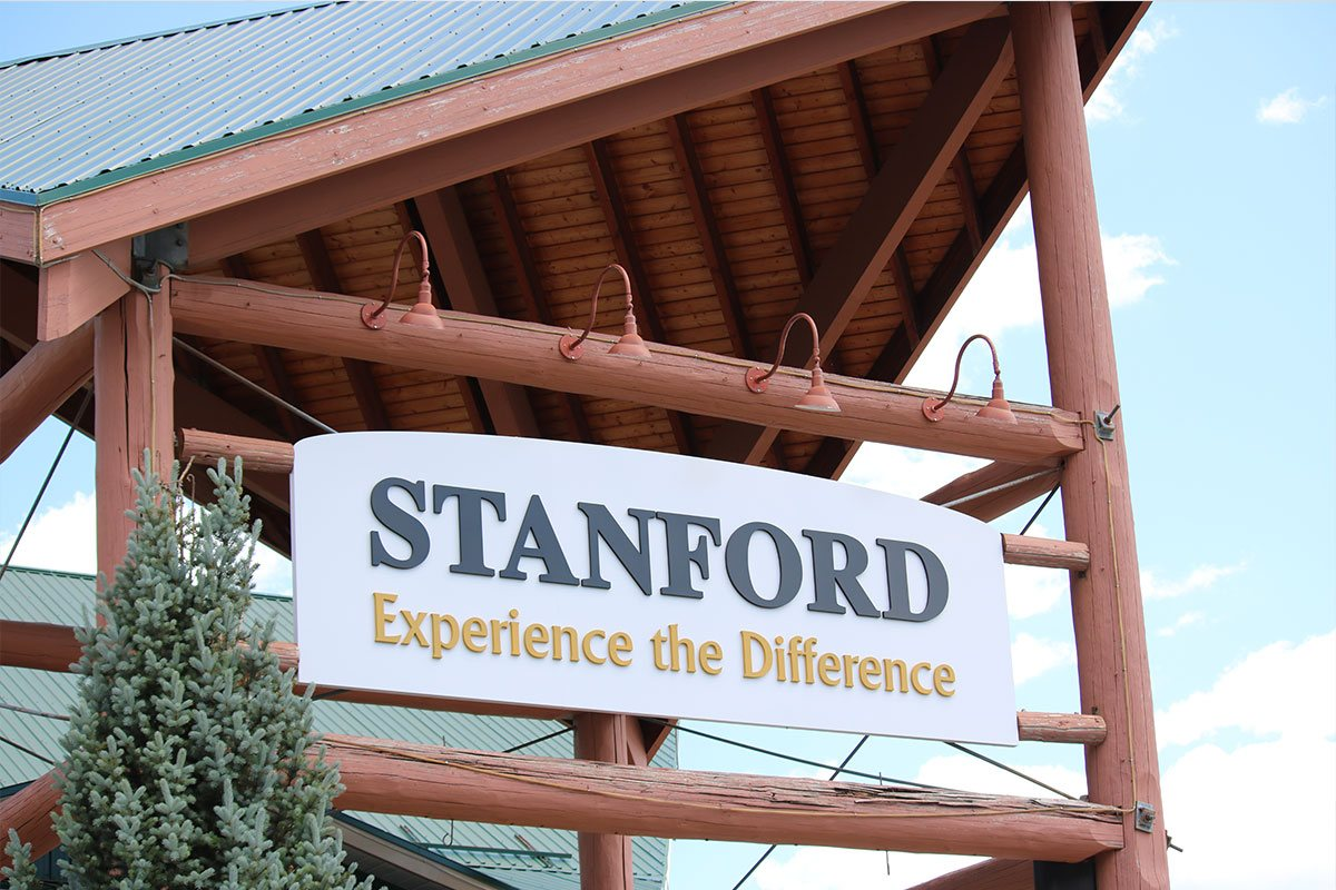The rectangular Stanford Fernie Resort sign has a white background with the corporate name Stanford in black lettering and slogan in yellow lettering Experience the Difference.
