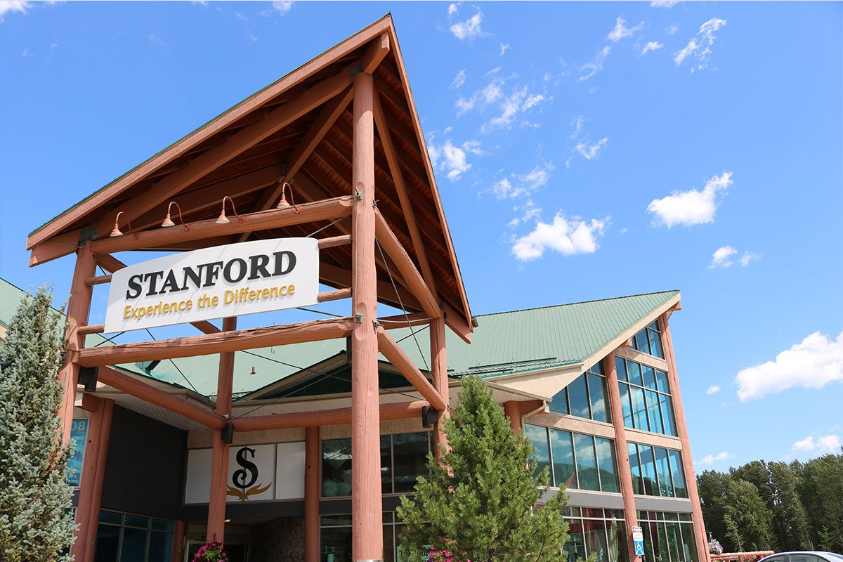 The triangular roof portico of the Stanford Fernie Resort from which hangs a white rectangular sign with the corporate name in black lettering and slogan Experience the difference written in yellow lettering.