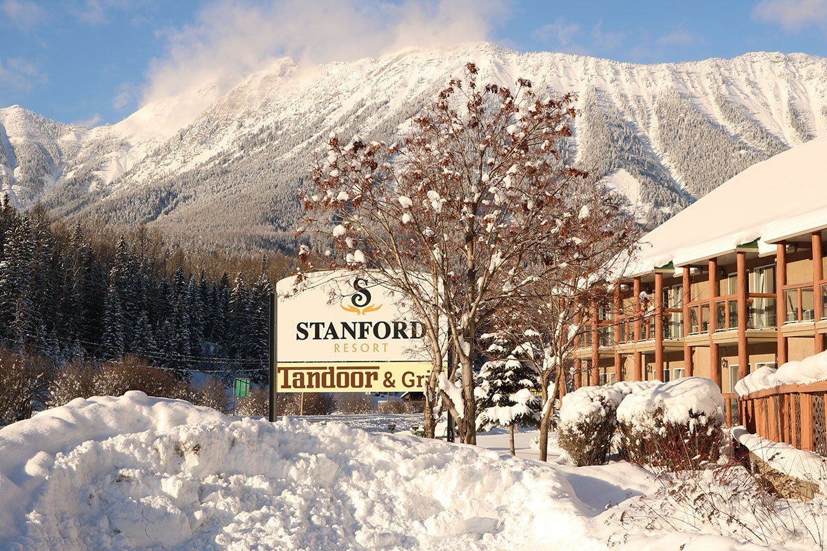 The Stanford Fernie Resort and Tandoor & Grill sign stands amongst snow covered trees, snow banks and the snow-capped Rocky Mountains in the background.