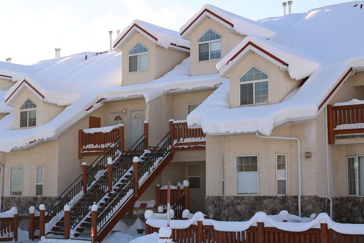 The exterior of a snow-covered multi-level condominium unit at Stanford Fernie Resort with a steel rod staircase leading to entrances protected by auburn brown wood balconies.