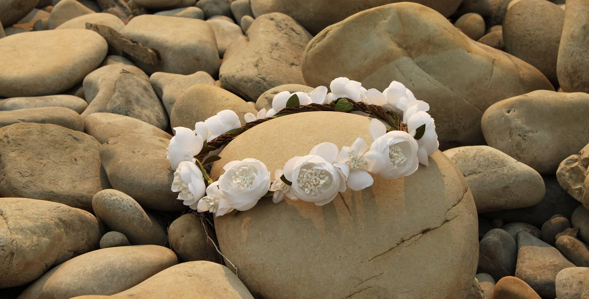 Pure white roses tied together in a bridal headband are placed amongst smooth cobbles and stones.