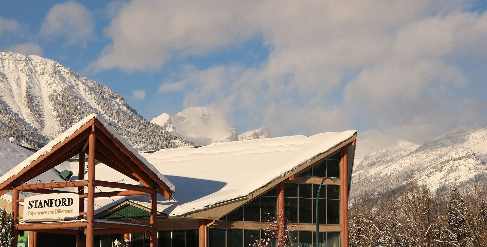 The snow-coated multi gabled rooftop of Stanford Fernie Resort stands in the foreground against the snow laden slopes and alpines trees of the Rocky Mountains on a bright sunny day.