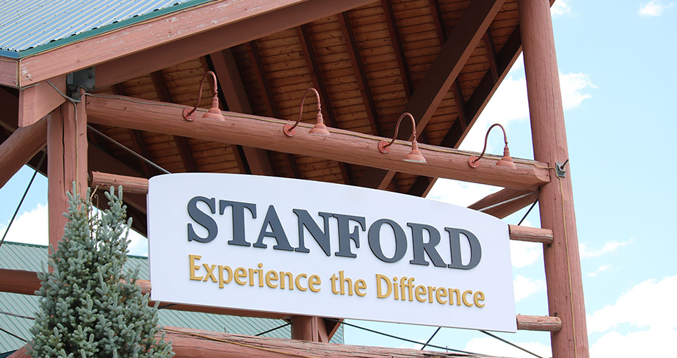 A view of the triangular shaped roof of the portico at the front entrance to Stanford Fernie Resort, bearing a large white rectanguar sign with the corporate name in black lettering and slogan in yellow lettering.