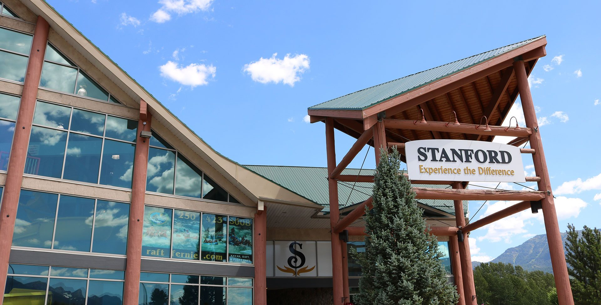 A skyward view of the triangular roof of the Stanford Fernie Resort building with ground to ceiling windows next to the triangular shaped roof portico bearing the company sign that greets visitors upon arrival.
