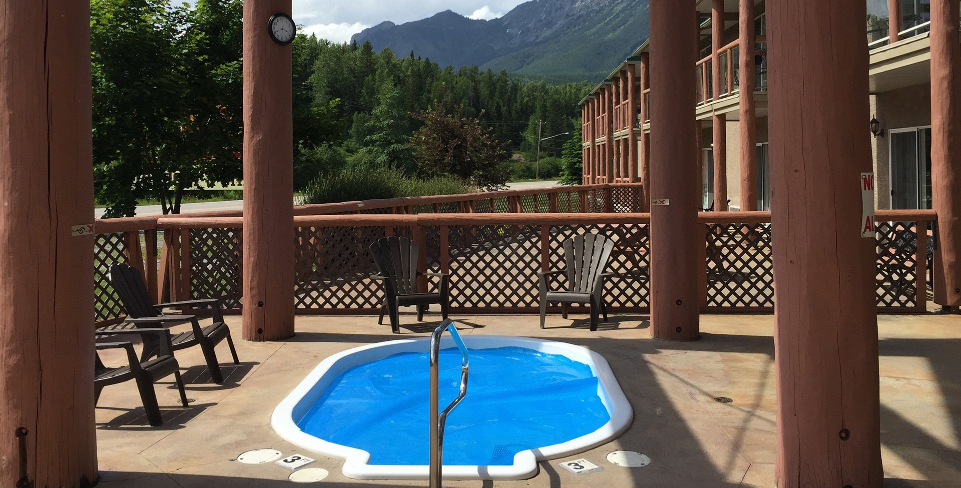 Four log posts surround the outdoor whirlpool area, at the Stanford Fernie Resort, featuring a round tub filled with crystal blue water, with four chocolate brown colored patio chairs placed around it.