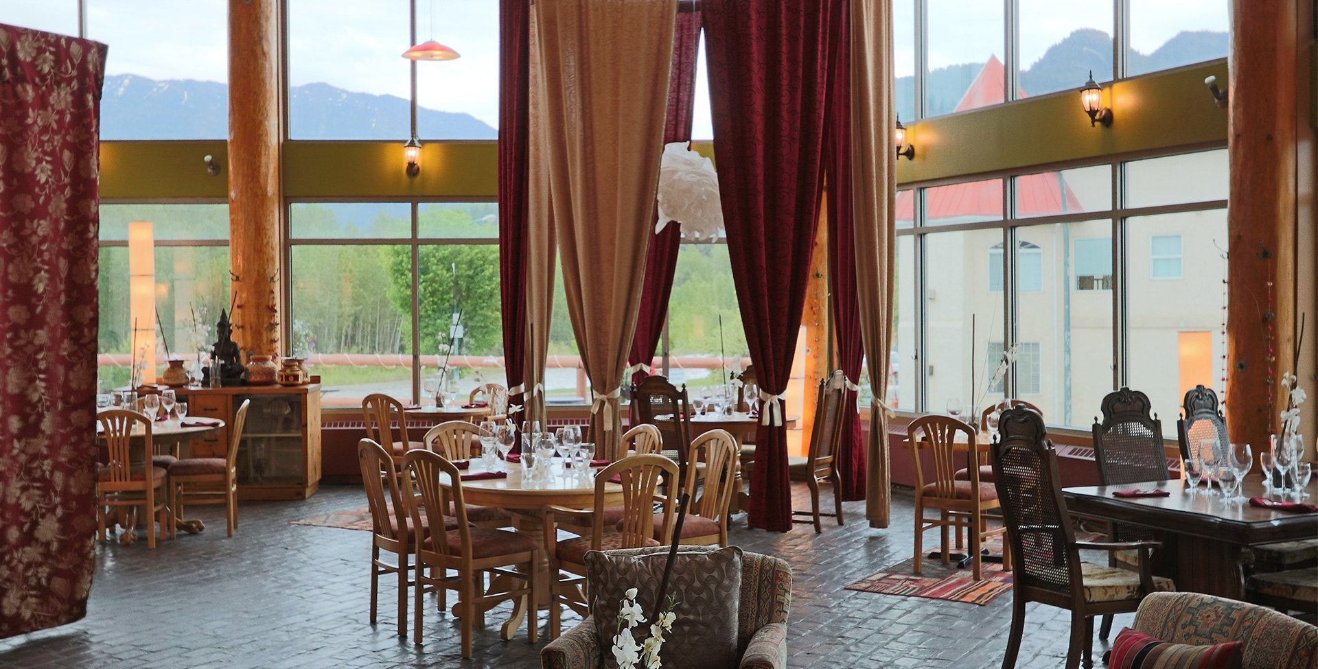 The dining room of the Tandoor & Grill Restaurant, located on the Stanford Fernie property showcases elegantly set tables placed before floor to ceiling windows reflecting scenic views of the Rocky Mountains with red and beige privacy curtains suspended from above.