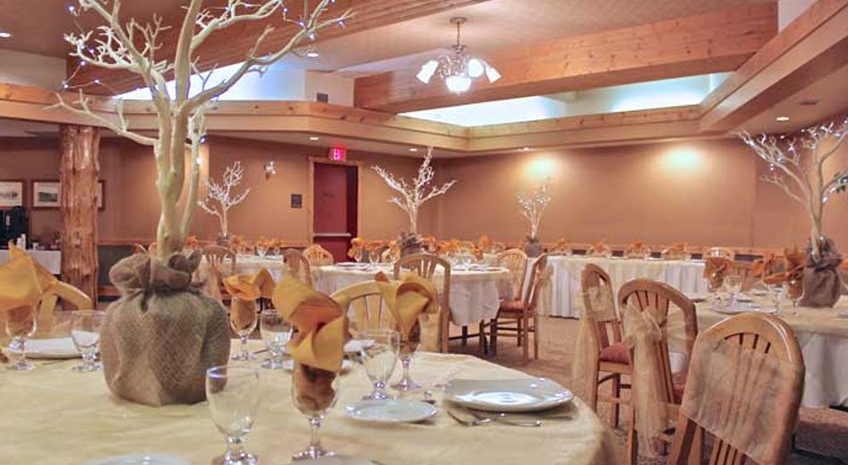 The Banquet Room at the Stanford Fernie Resort features elegantly set banquet tables with barren trees as centerpieces with its' branches decorated with lights and a brown burlap wrapping used as a base stand.