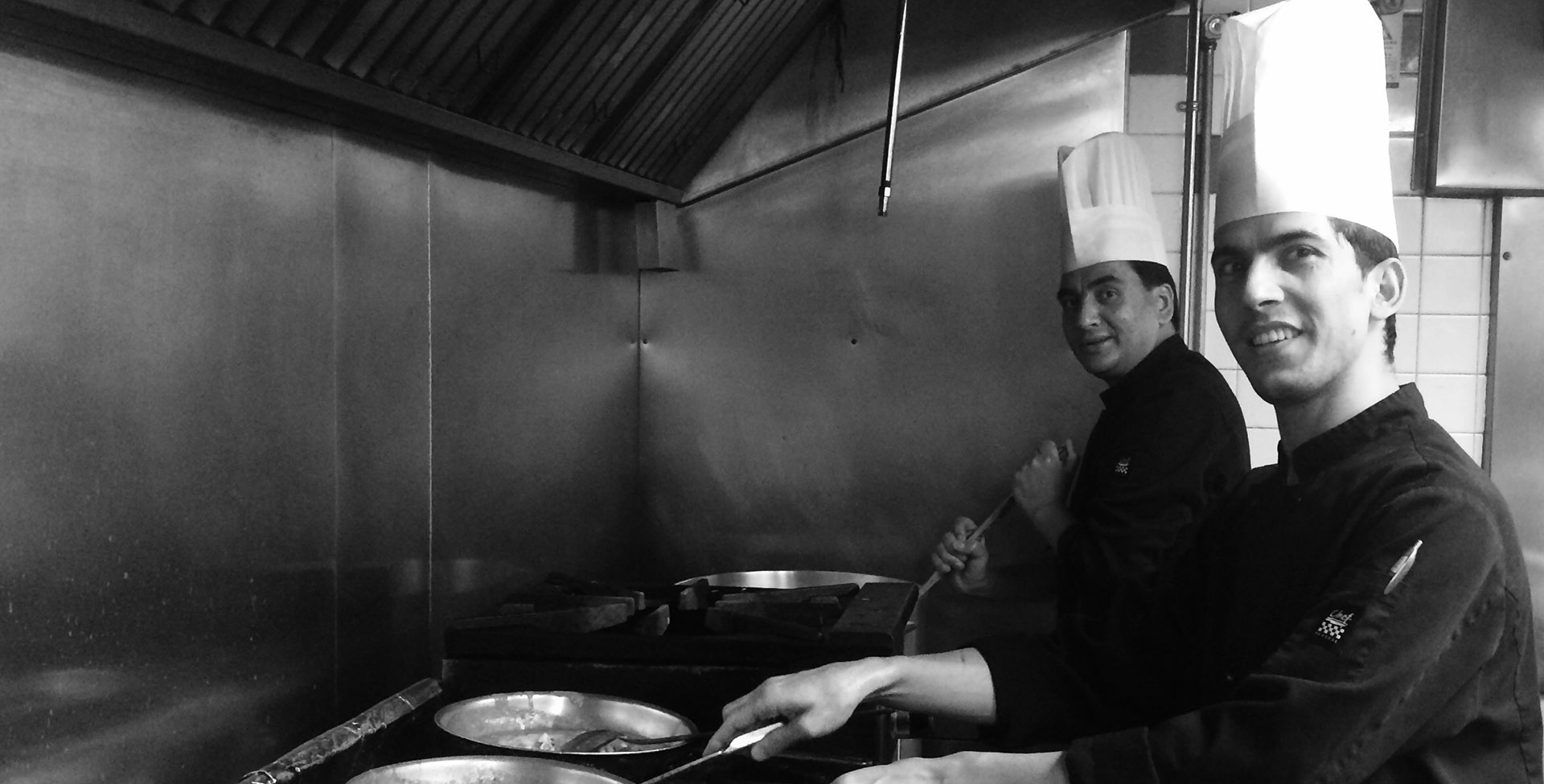 A black and white photo of two chefs wearing tall chef's hats at work over gas ranges and skillets in the kitchen at the Tandoor & Grill, the onsite restaurant at the Stanford Fernie Resort.