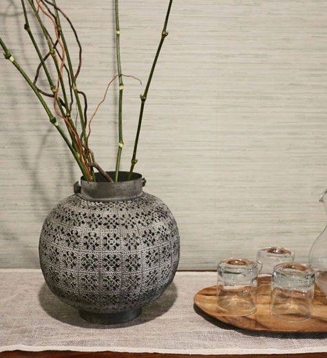 Long thin green horsetail plants are placed in a rotund silver metallic vase with filigree design next to three drinking glasses on a wood slab at Evoke Spa located at the Stanford Fernie Resort.