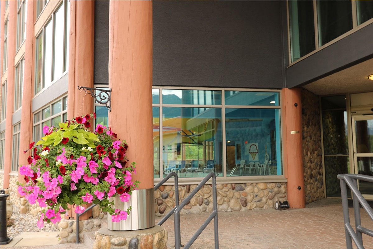 Large log columns, concrete and stone walls, large picture windows and an arrangement of red and pink petunias are features of the front entrance to the Stanford Fernie Resort .