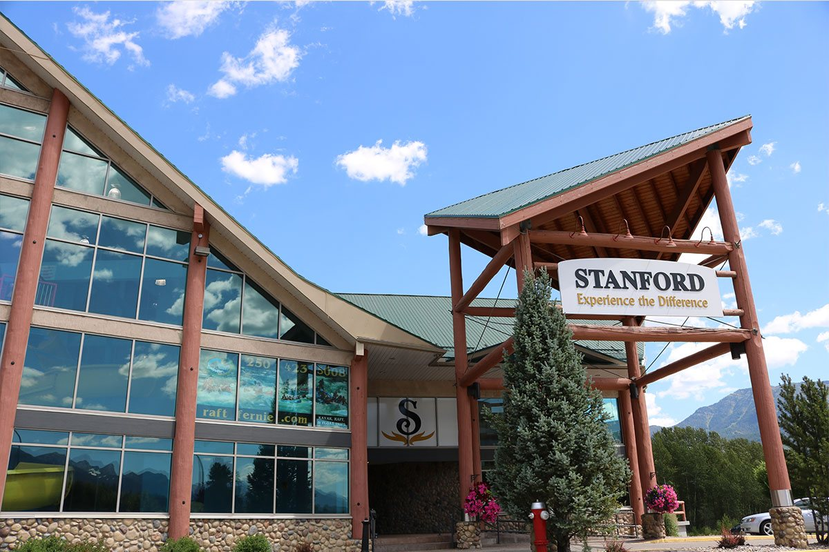 A panoramic view of the entrance to the Stanford Fernie Resort featureing a bright red fire hydrant built beside a tall pine tree and a towering log portico with a triangular roof.