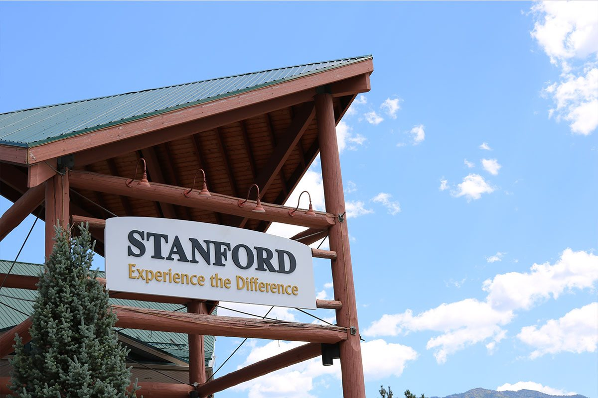 The corporate sign with the company slogan hangs high up on the log built portico structure at the front entrance of the Stanford Fernie Resort on a bright and clear day.