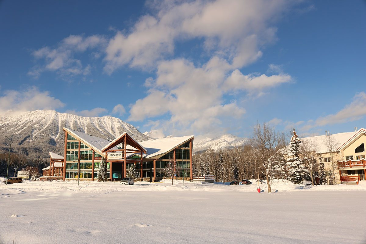 Exterior view of the Stanford Fernie Resort in the winter, with a triangular shaped portico and multi gabled roof structure of the hotel in the foreground and the snow covered Rocky Mountains in the background.