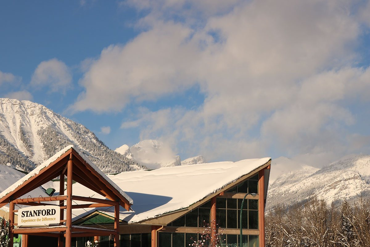 A view of the snow covered triangular roofs of the portico and the Stanford Fernie Resort pointing northward with billowing white clouds above and the Rocky Mountains blanketed in snow in the distance.