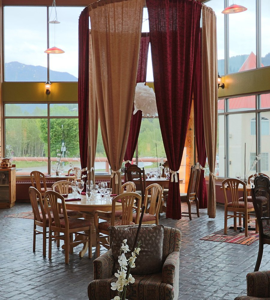 In the dining room of the Tandoor & Grill Restaurant, located onsite at the Stanford Fernie Resort, red and beige privacy curtains surround a table placed before floor to ceiling windows looking out toward scenic views of the Elk River banks in BC.