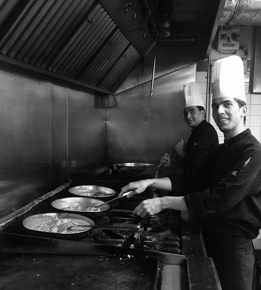 A black and white photo of two chefs preparing skillets of food over gas stove ranges at the Tandoor & Grill Restaurant, on the premises of the Stanford Fernie Resort in BC.