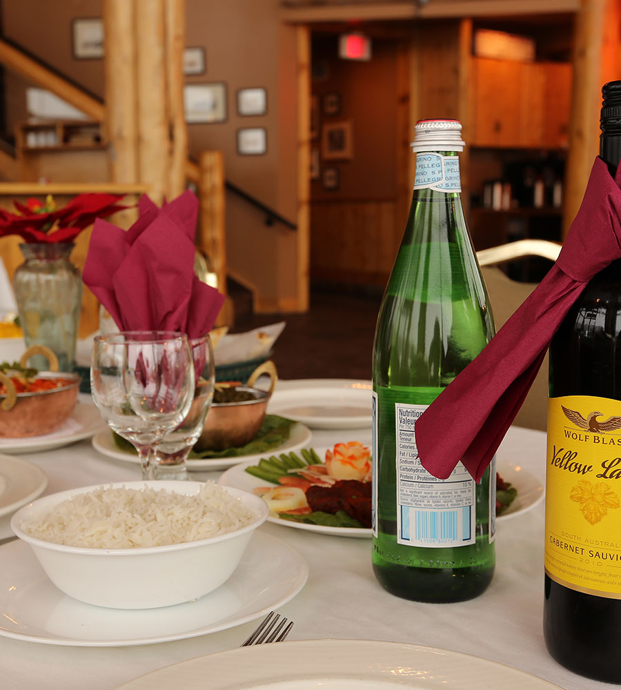 At the Tandoor & Grill Restaurant, onsite at the Stanford Fernie Resort, a table is set with bottles of mineral water and wine, wine glasses, a bowl of white rice alongside a plate of chicken tikka with garnishes.