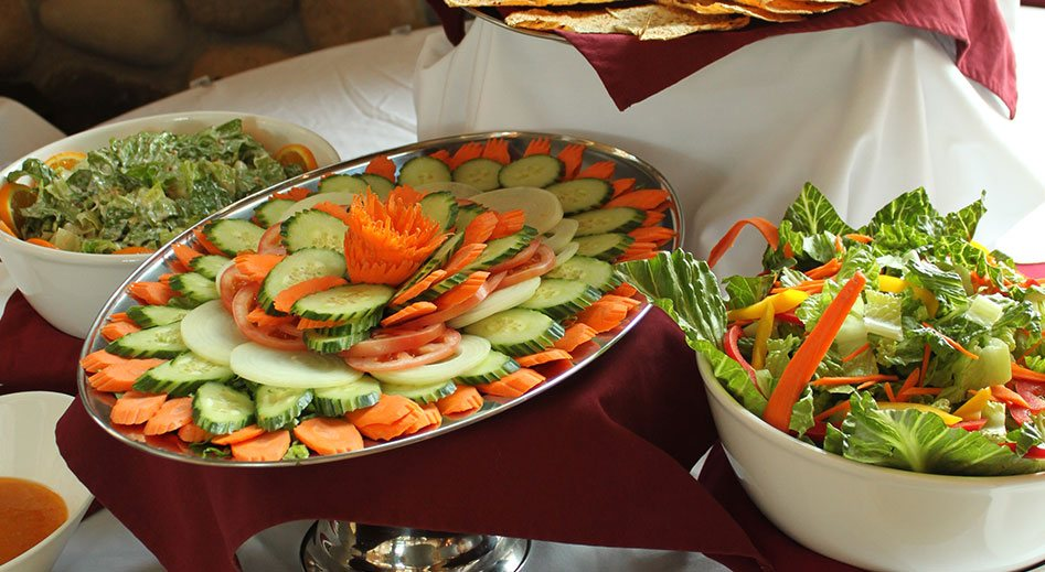 White bowls of salad are placed around a silver platter of sliced carrots, cucumbers, onions and tomatoes arranged in concentric circles.