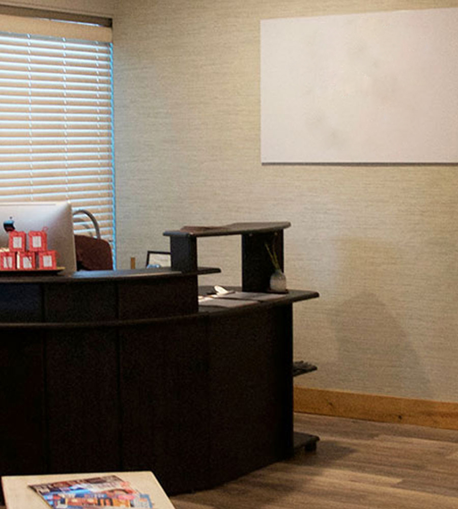 The wrap around front desk of Evoke Spa sits in front of closed venetian blinds next to the corporate sign hung from beige colored walls on the premises of the Stanford Fernie Resort in British Columbia.