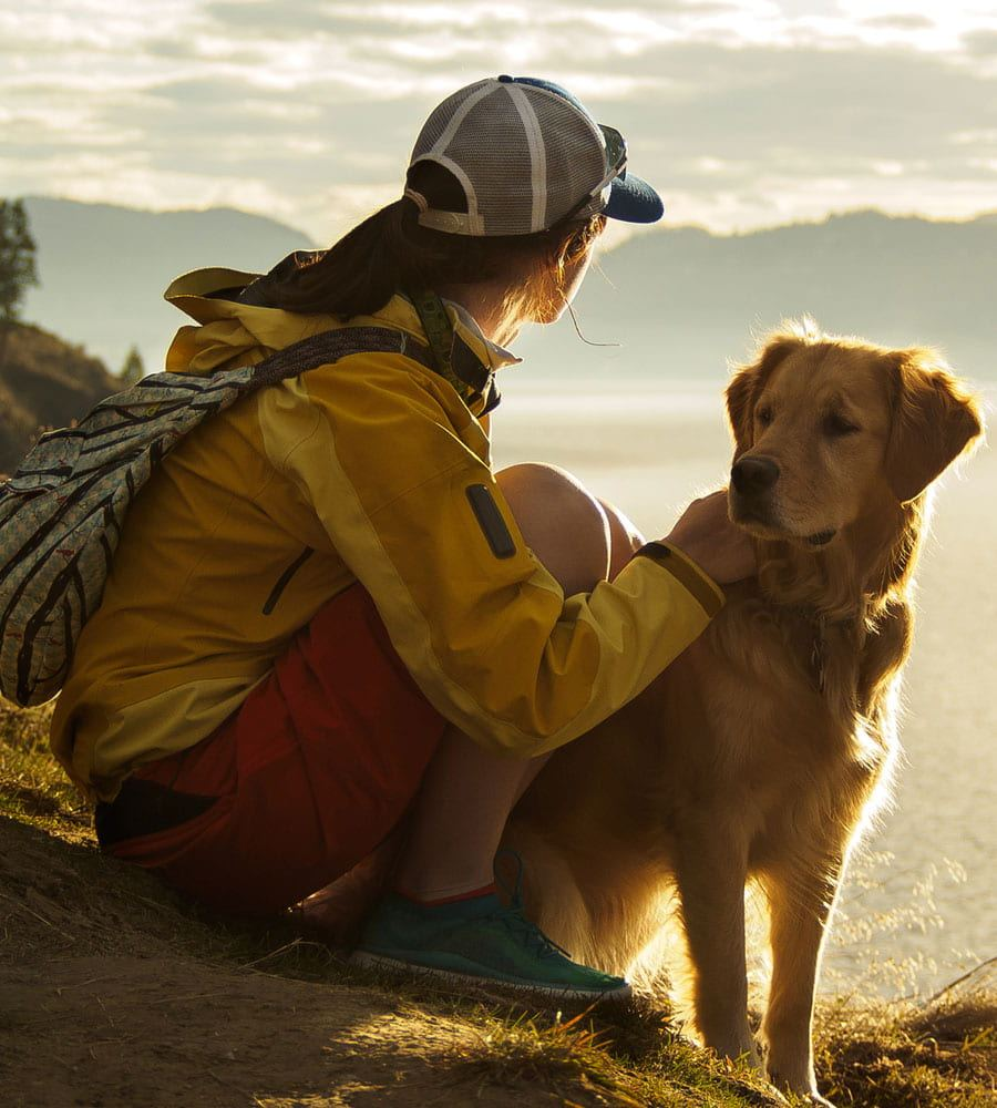 A young female wearing a baseball cap, yellow jacket and red shorts sits by her pet golden retriever looking out over the Rocky Mountains on a sunny day in Fernie, BC.