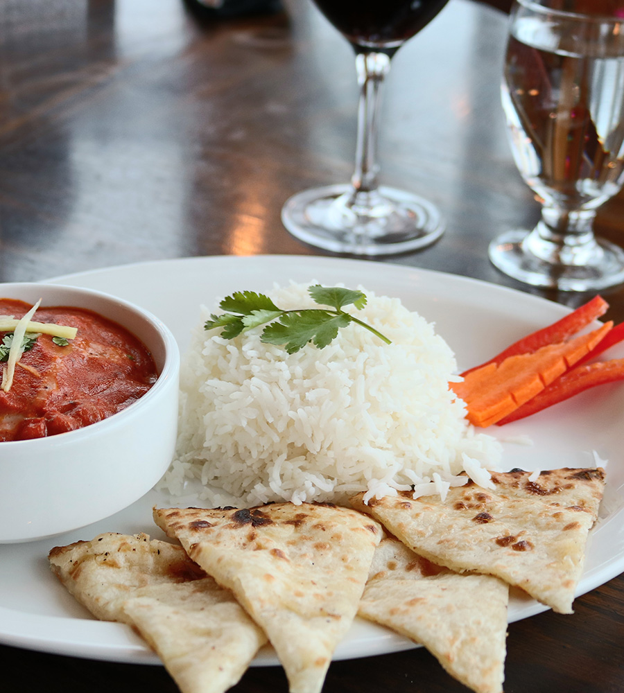 The Tandoor & Grill Restaurant at the Stanford Fernie Resort serves a plate of white rice topped with parsley, triangular shaped dosas, a bowl of dipping sauce and carrot and red pepper garnishes.