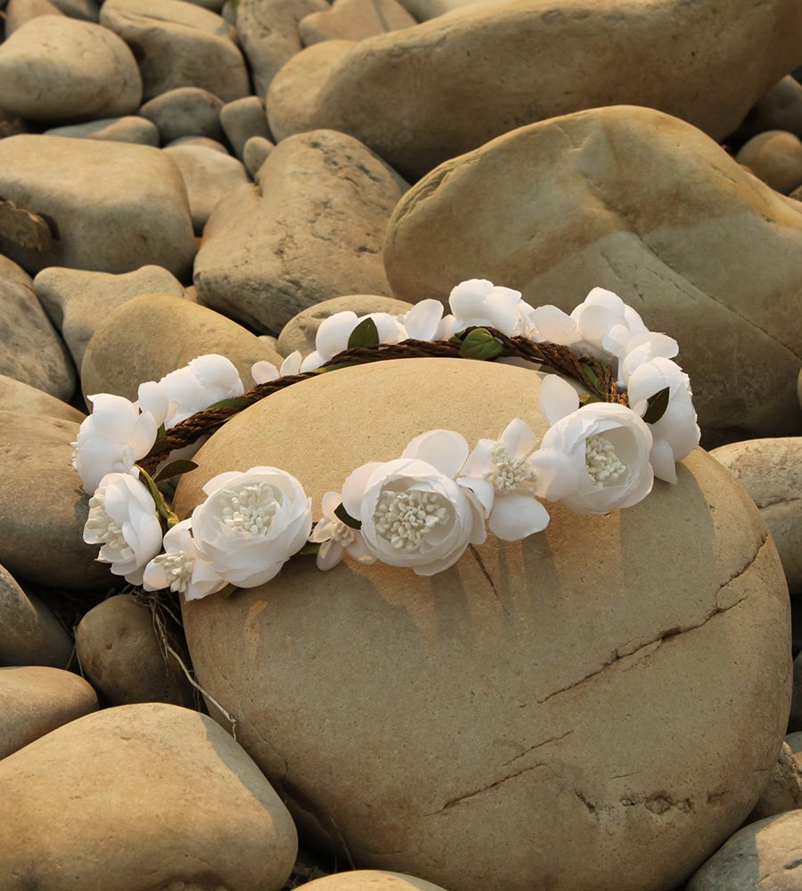 A bridal headband made entirely of white roses lay amongst smooth off-white cobblestones.