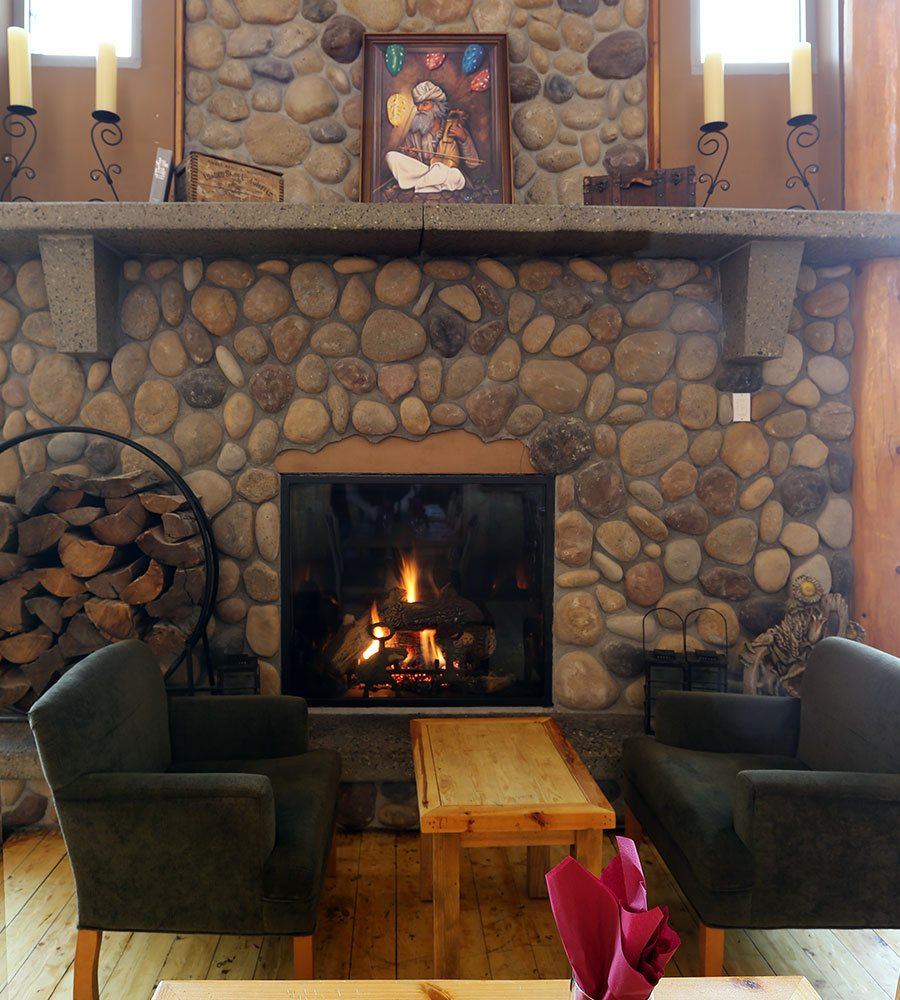 A common lounge area at Stanford Fernie Resort features two charcoal grey arm chairs placed between a rustic coffee table in front of a wood burning cobblestone fireplace.