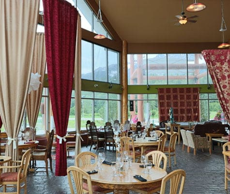 The dining area of the Tandoor & Grill, the onsite restaurant at the Stanford Fernie Resort showcases round beige wood dining table and chair sets and red, beige and red and gold print privacy curtains suspended from rods above.