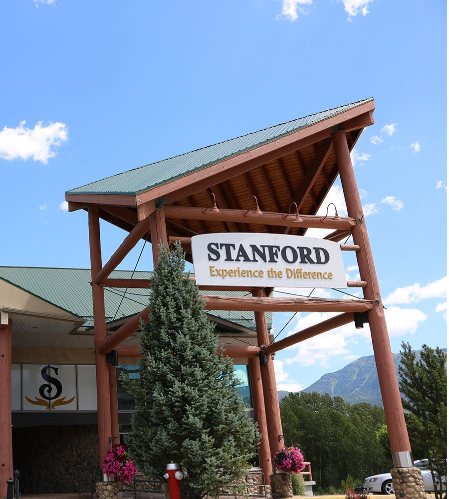 Pink petunia arrangements, a bright red fire hydrant and a towering conifer tree are placed by the foot of the log portico structure leading to the front entrance of the Stanford Fernie Resort