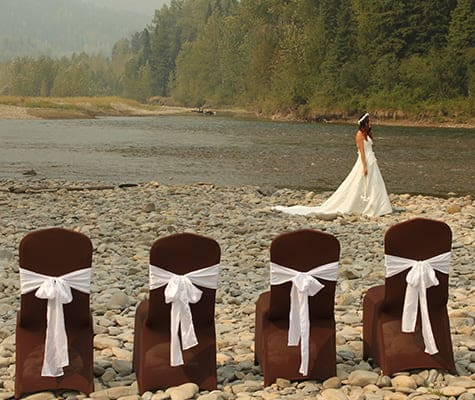 A row of four chairs covered in brown slipcovers tied with a large white bow are placed on a cobblestone river bank of the Elk River with a female dressed in a sleeveless wedding gown in the background.