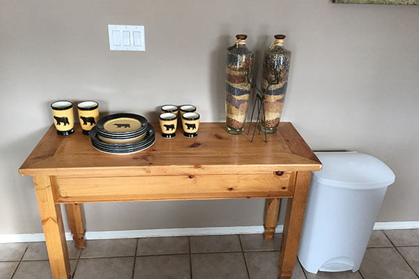 A set of plates and cups and two decorative bottles sit on a four legged beige-brown wood stained side table placed against a grey wall in a suite at Stanford Fernie Resort in BC.