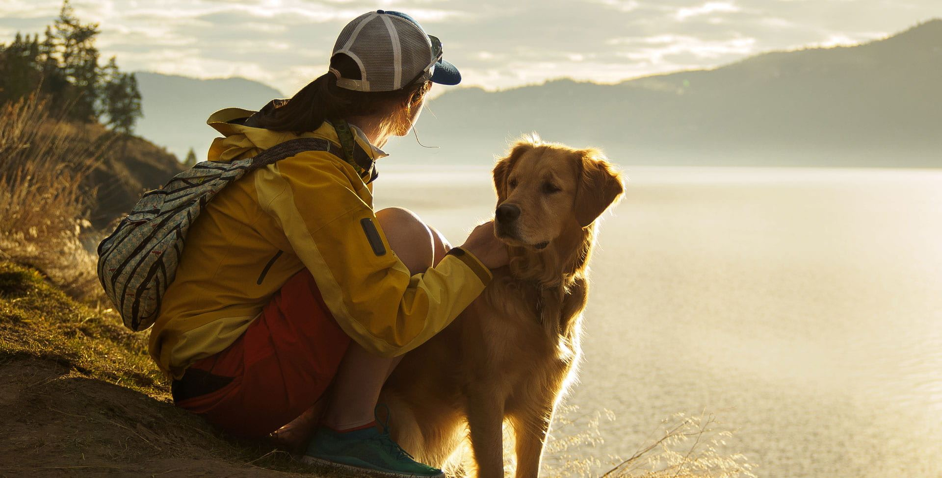A young woman wearing a baseball cap, yellow jacket and red shorts looks out over a lake and mountains to the distance with her pet golden retriever by her side.