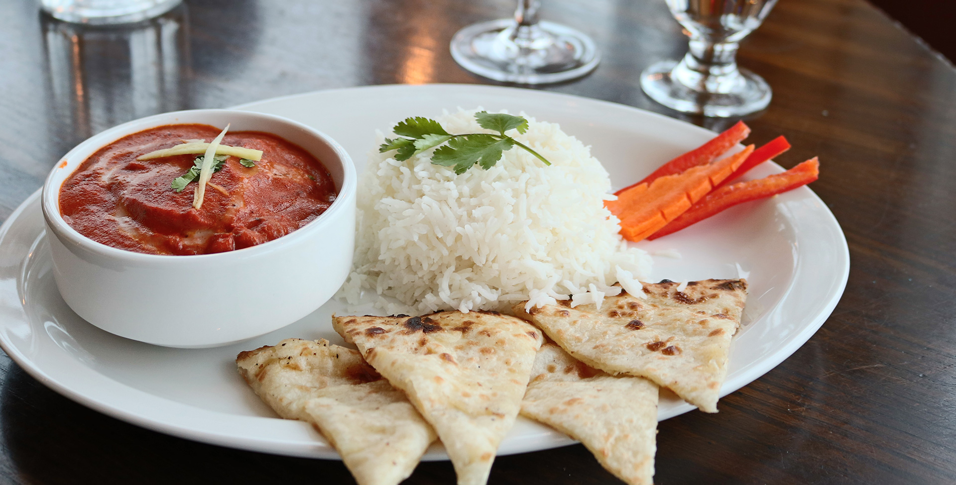 A round white plate serves a round container of red dipping sauce, dosas, white rice topped with parsley and carrots and red pepper garnishes at the Tandoor & Grill restaurant at Stanford Fernie Resort.