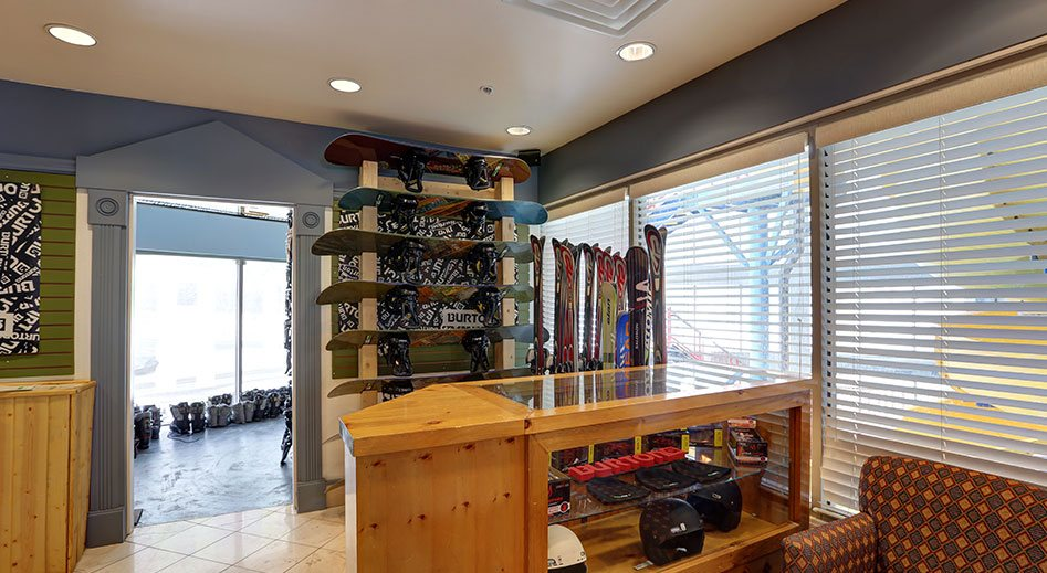 The interior of SnowPro Rentals onsite at Stanford Fernie Resort features a tall shelf of snowboards, skis placed up against a window covered by white blinds and a wood and glass display case of helmets.