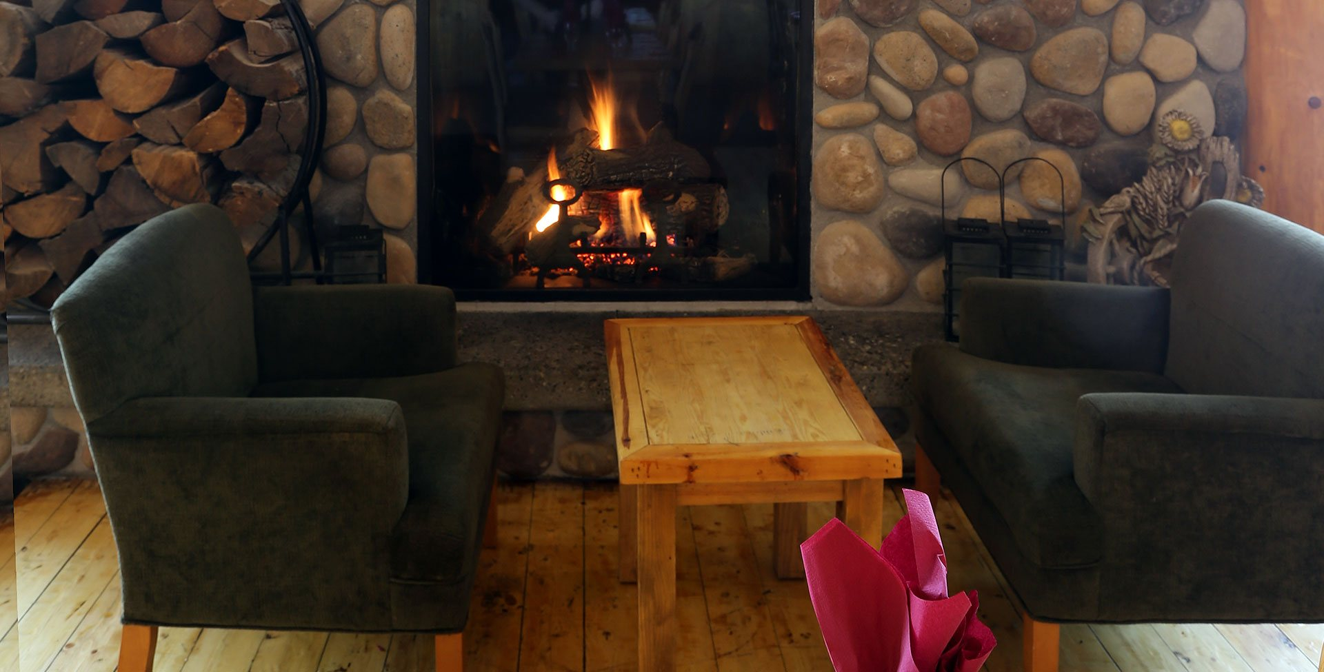 At the Stanford Fernie Resort, two charcoal colored arm chairs sit between a rustic square coffee table that are part of the lounging area with a stone woodburning fireplace.
