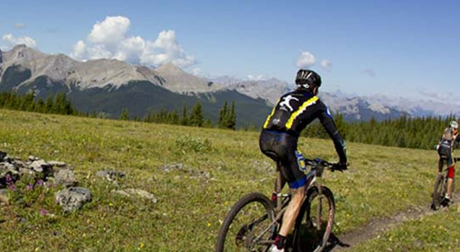 Two male mountain bikers on a bike trail ride past green pastures and rocks against a view of the snow capped Rocky Mountains in the distance in Fernie, BC.