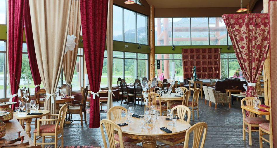 The dining space of the Tandoor & Grill Restaurant, onsite at the Stanford Fernie Resort, features floor to ceiling windows and round natural beige wood dining table sets with high-backed wood chairs to match.