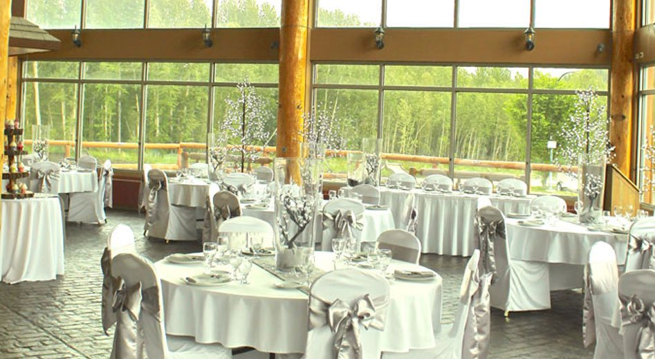 The Great Room at the Stanford Fernie Resort, features elegantly set white dining tables and chairs and three storey floor to ceilings windows looking out onto vibrant green trees and the Rocky Mountains.