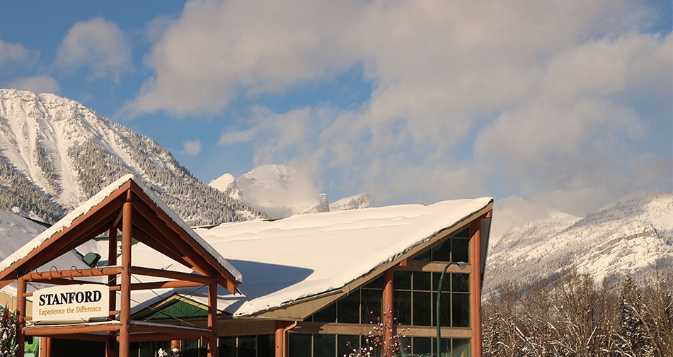 A view of the snow covered gabled rooftop and gabled portico structures of the Stanford Fernie Resort set against the towering  snow laden summit of the Rocky Mountains in BC.